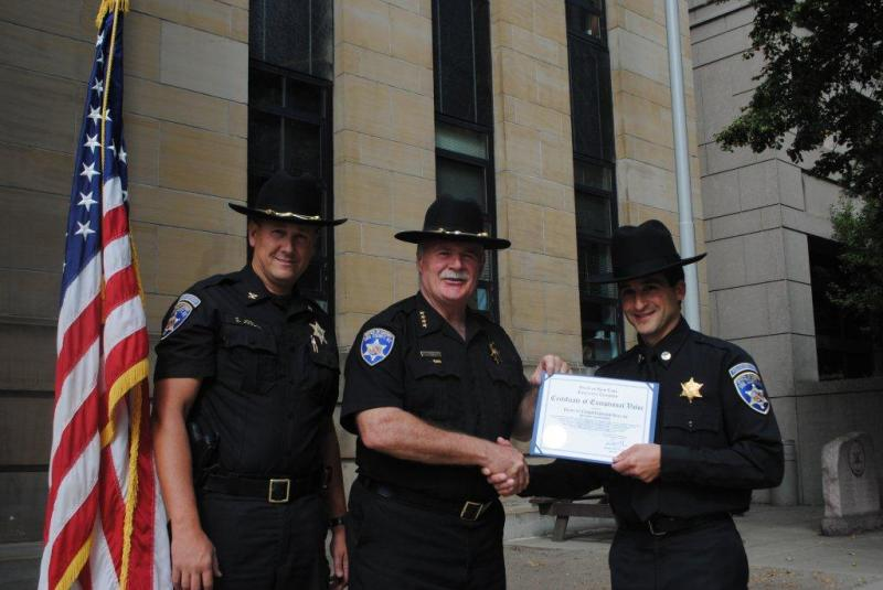 Sheriff Tim Howard and Chief Scott Joslyn present an award for valor to Deputy Christopher Soluri